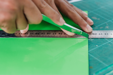 Close-up to hands of students are cutting  prints and stickers  using knife cutter.