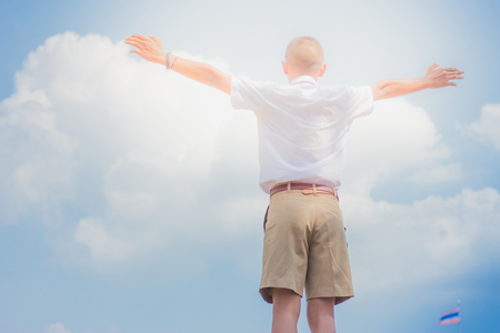 Student acting like a superhero on top of stepladder in school. Stock Photo