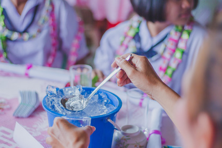 Close-up of hands add ice to the glass to distribute to friends at the table on party of Graduation. Stock Photo