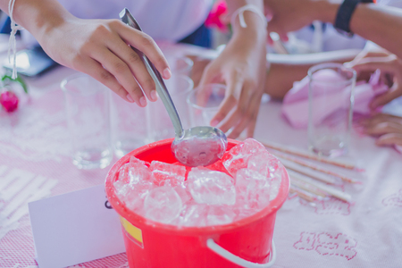 Close-up th hands add ice to the glass to distribute to friends at the table on party of Graduation.