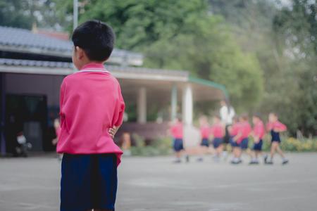 Kindergarten student stands alone because he is punished by teacher. Standard-Bild
