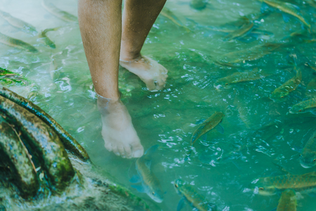 Fish spa, clean foot, healthcare concept with child at Arawan waterfall Kanchanaburi, Thailand Stockfoto