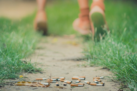 No Smoking concept. Smoking student is running away from his teacher in school. Selective focus on cigarette.