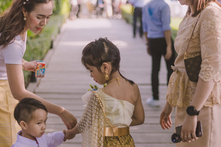 KANCHANABURI THAILAND -FEBRUARY 11 : Unidentified girl and boy in thai costumes wait to welcome and give flowers to the grooms parade in Thai Wedding Ceremony   at Brides house on February 11,2018  in Kanchanaburi, Thailand