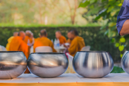 To make merit by offering food to monk ceremony in Thai wedding tradition.Selective focus on alms bowl.