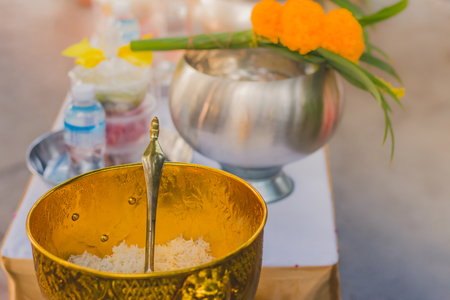 To make merit by offering food to monk ceremony in Thai wedding tradition. Selective focus on rice ladle. Stock Photo