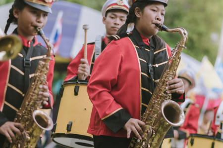 KANCHANABURI THAILAND - JULY 18 :   Thai school marching band on street, in athletic game opening day of primary student in the rain on July 18,2018 at Nongthabong School in Kanchanaburi, Thailand Imagens - 124658529