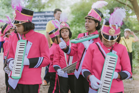 KANCHANABURI THAILAND - JULY 18 :   Thai school marching band on street, in athletic game opening day of primary student in the rain on July 18,2018 at Nongthabong School in Kanchanaburi, Thailand Imagens - 124658533