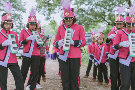 KANCHANABURI THAILAND - JULY 18 :   Thai school marching band on street, in athletic game opening day of primary student in the rain on July 18,2018 at Nongthabong School in Kanchanaburi, Thailand Imagens - 124658534