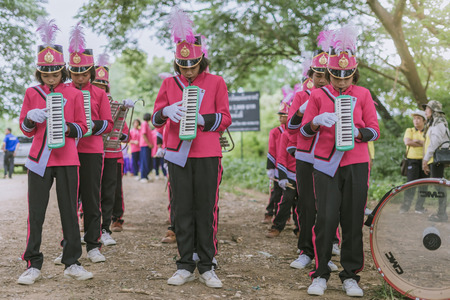 KANCHANABURI THAILAND - JULY 18 :   Thai school marching band on street, in athletic game opening day of primary student in the rain on July 18,2018 at Nongthabong School in Kanchanaburi, Thailand Imagens - 124658535