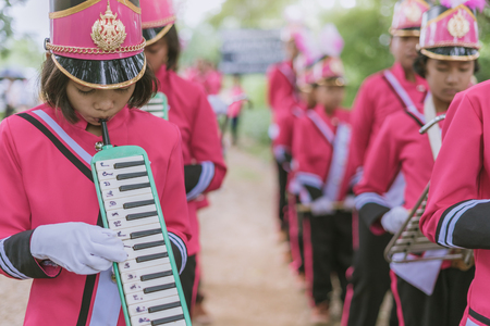 KANCHANABURI THAILAND - JULY 18 :   Thai school marching band on street, in athletic game opening day of primary student in the rain on July 18,2018 at Nongthabong School in Kanchanaburi, Thailand Imagens - 124658536