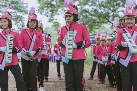 KANCHANABURI THAILAND - JULY 18 :   Thai school marching band on street, in athletic game opening day of primary student in the rain on July 18,2018 at Nongthabong School in Kanchanaburi, Thailand Imagens - 124658600