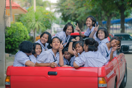 KANCHANABURI THAILAND - JULY 26 :   Students sit in the back of pickup truck to go to temple in traditional lent candle festival for Buddhist Lent Day on July 26,2018 at Watkrangthongratburana school in Kanchanaburi, Thailand