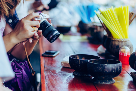 Young woman prepares a camera ready to take a photo at riverside of Amphawa, Thailand