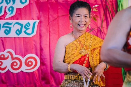 KANCHANABURI THAILAND - SEPTEMBER 28 :   Unidentiffied female teachers perform Thai dance on stage for retirement on September 28,2018 at Watkrangthongratburana school in Kanchanaburi, Thailand 에디토리얼