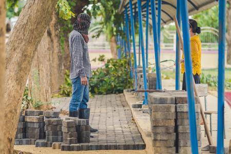 Conserje de la escuela construye un camino de ladrillos en la escuela Editorial