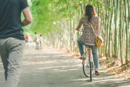Happiness couple ride a bicycle in the bamboo park