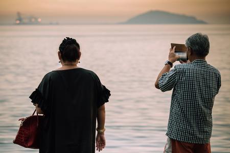 Happiness Mature couple take a photo of sunset at the beach. Standard-Bild