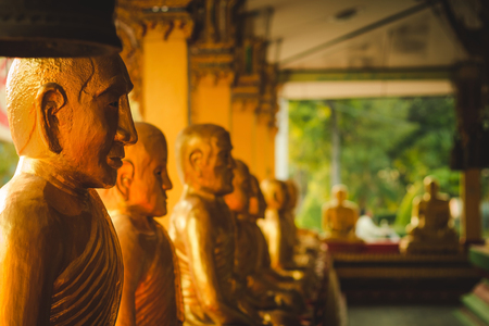 A row of golden buddha statue at Wat Intharam Kanchanaburi, Thailand.