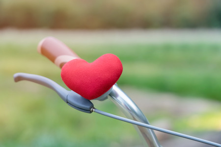 A little red heart pillow on the bicycle handlebar.