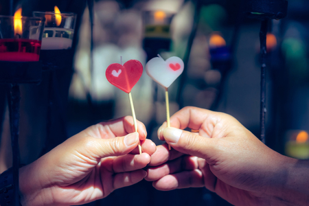 Romantic couple on valentines day. Happy joyful couple give heart candle to each other in front of candle light, Love concept.