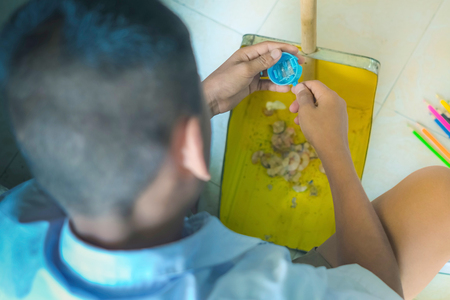 Elementary student sharpen the color pencil into the dustpan in front of classroom