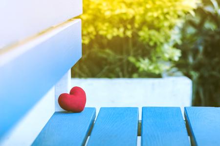 A little red heart pillow on chair in garden.
