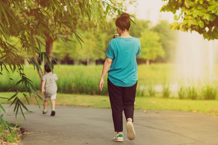Back view of mom and son walk for excercise together before sunset in public park