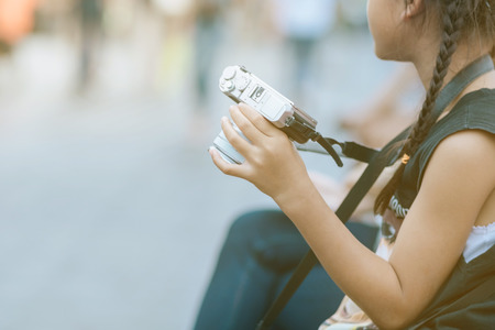 Asian girl learning to use a mirrorless camera with her mom in the public park. Selective focus on hand.
