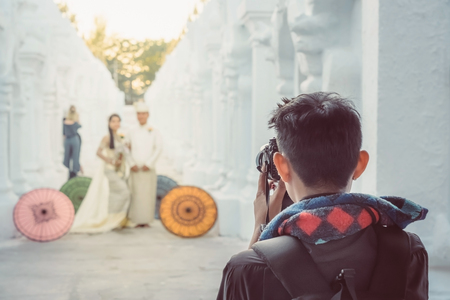 Myanmar wedding photography. A Burmese couple in a tradition dress that was photographed by a wedding photographer and his assistant in a famous temple. Villagers believe this brings good luck to young couples. Selective focus on photographer assistant. Stock Photo