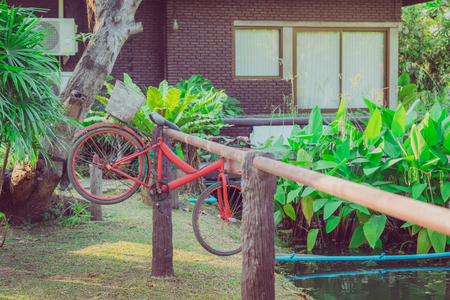 The old red bike hangs on a steel rail near the pool to decorate the garden. Stock fotó