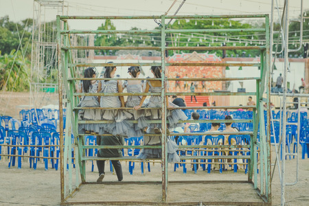 Young girls sit on the grandstand to wait for the stage performance. Imagens