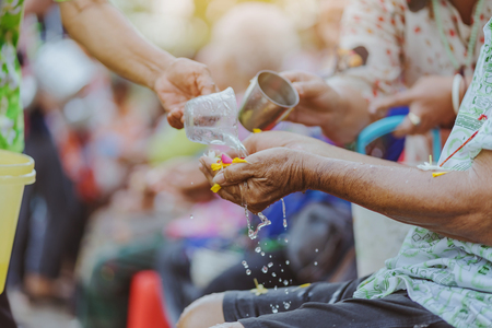 Thai people celebrate Songkran by pouring water and giving garlands to elder senior or respected grandparents and elder and asked for blessings for celebrate Songkran in new year water festival 免版税图像