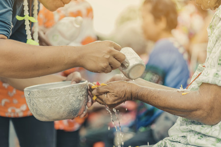Thai people celebrate Songkran by pouring water and giving garlands to elder senior or respected grandparents and elder and asked for blessings for celebrate Songkran in new year water festival Editorial