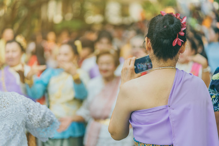 Back view of people take a photo by smartphone of a Thai dance parade in Songkran festival in Kanchanaburi Thailand.