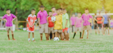Blur of Asian boys practice kicking the ball to score goals in the public football field. Imagens