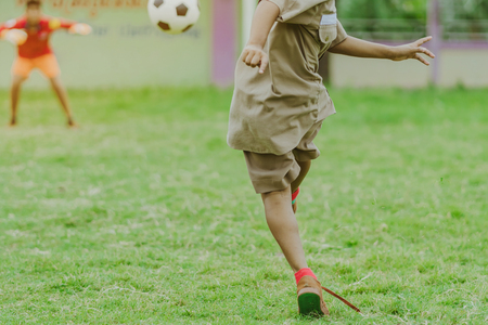Asian boys practice kicking the ball to score goals in the public football field.