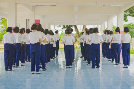 Group of students try to meditate for the peace of mind by walk with Buddhist monk in school.