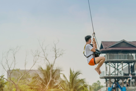 A male tourist flying on a zipline aka flying fox across the lake at Pattaya Floating Market, Thailand. Imagens