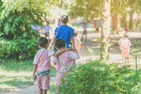 Kindergarten boy walk after female teacher and his friends back to class after having lunch.