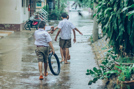 Boy students leave the classroom to walk on the street after heavy rain in the school.