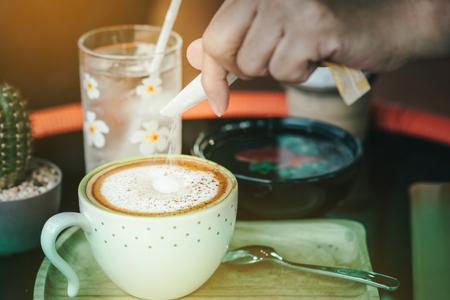 Frau gießt Zucker in eine weiße Tasse Kaffee, selektiver Fokus auf Zuckerpakete. Standard-Bild