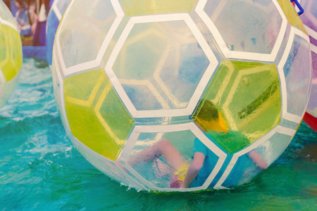 Kid having fun in giant bubble ball on water in the swimming pool at the theme park in annual festival.