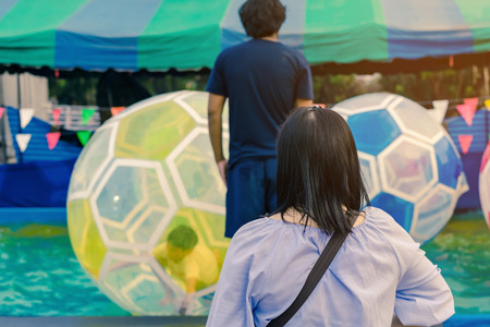 Mom and dad watching their son having fun in giant bubble ball on water in the swimming pool at the theme park in annual festival.