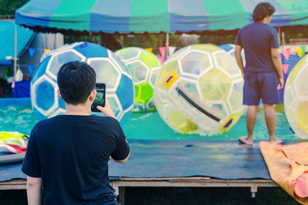 Dad take a photo by smartphone of his son having fun in giant bubble ball on water in the swimming pool at the theme park in annual festival.