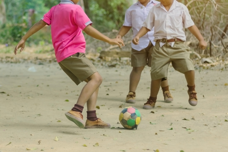Student enjoy to play the old football with his friends on the ground in school.