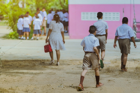 Back view of the teacher and the students walking go to study at the classroom in the building