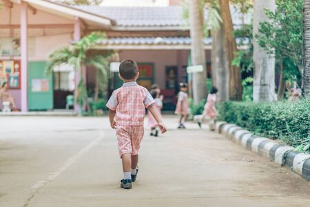Back view of Boy followed girl friends on street to go to the classroom in school.
