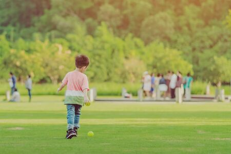 Kid enjoy to playing with little ball on green field Imagens