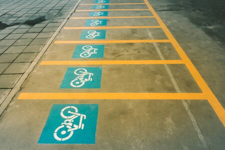 A white painting of a bicycle on the asphalt of the road that means mark of bicycle parking area.